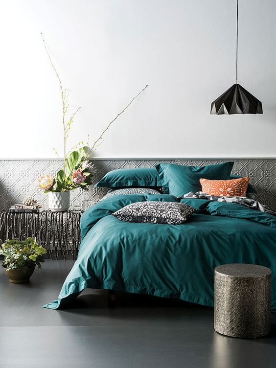 an emerald bedding with patterned rust and black pillows for a bold touch