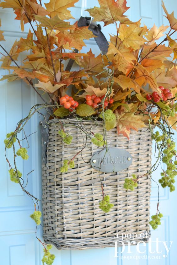 a basket with fall leaves, cascading greenery and berries can be used instead of a usual fall wreath