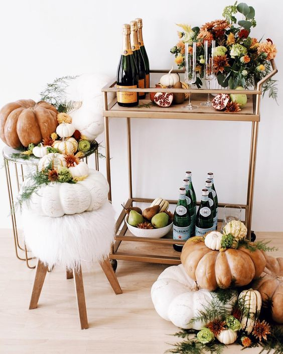 a gorgeous fall bar cart with a bright floral arrangement, pumpkins, pomegranates and pears in a bowl