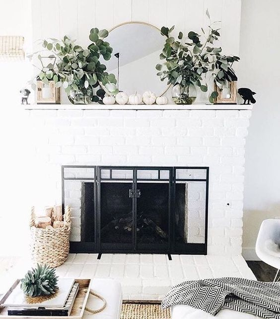 a modern mantel with eucalyptus branches in sheer vases, lanterns and white pumpkins