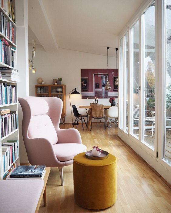a pink chair and a mustard velvet ottoman fore creating a bright fall nook for reading and relaxing