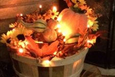 15 a fall bushel basket filled with fake leaves, blooms, gourds, pumpkins and lights