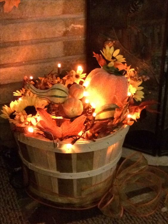 a fall bushel basket filled with fake leaves, blooms, gourds, pumpkins and lights