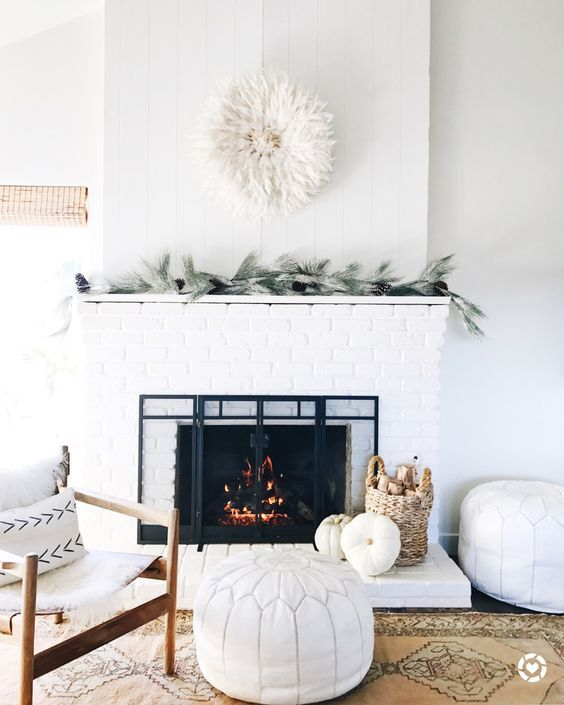 a simple modern mantel with evergreens, pinecones, a corn husk wreath, pumpkins and branches in a basket