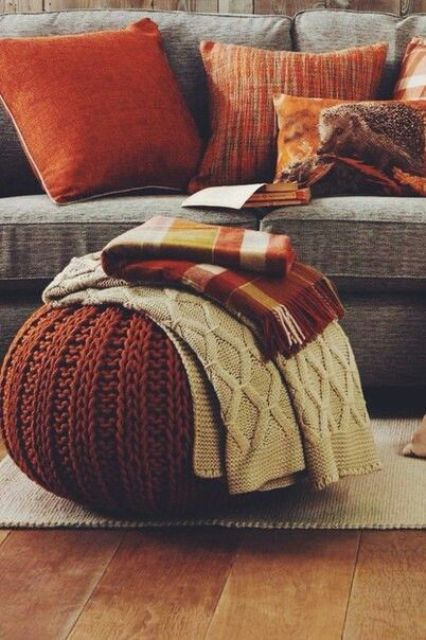 rust-colored pillows and a chunky knit ottoman for a cozy feel in your space