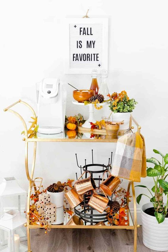 an amazing fall bar cart with copper mugs, plaid towels, greenery, fake pumpkins and pinecones