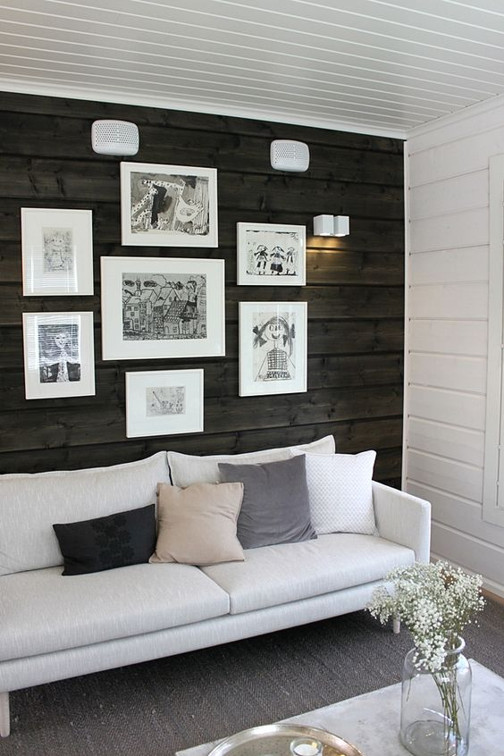 a dark stained wood accent wall stands out a lot in this white space and adds coziness