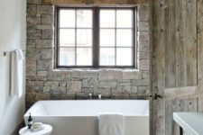 27 a stone accent wall highlights the chalet feel of this bathroom