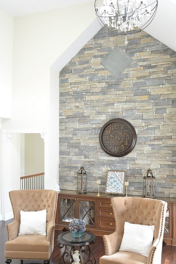 this elegant vintage space is spruced up with a stone accent wall that highlights the roof shape