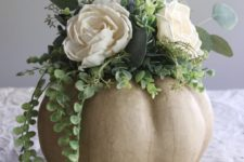 DIY craft pumpkin centerpiece with neutral blooms and greenery
