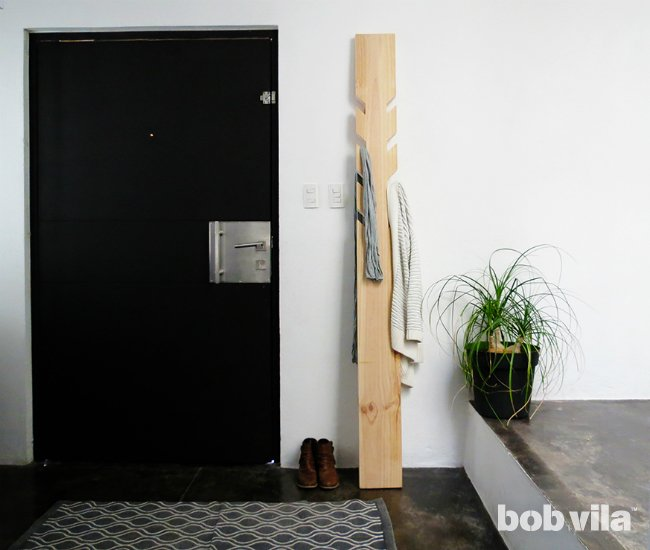 DIY modern coat rack of a wooden slab and cutout hooks (via www.bobvila.com)