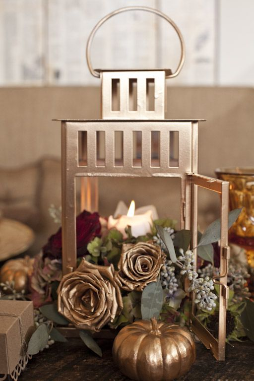 IKEA Borrby lantern spray painted copper with foliage, blooms, fake pumpkins and flowers and candles is a great fall centerpiece
