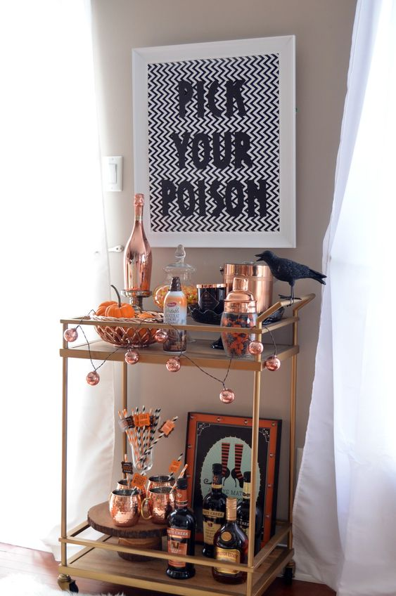 a Halloween bar cart with copper touches, a black bird, a sign and a garland for a bright look