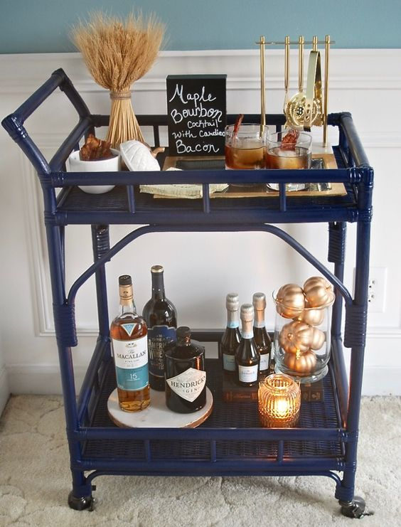 a Thanksgiving bar cart with wheat, gilded pumpkins and a candle in a candle holder