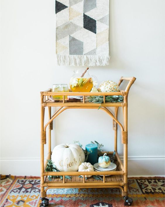 a Thanksgiving cart with painted pumpkins, greenery and a boho artwork over it