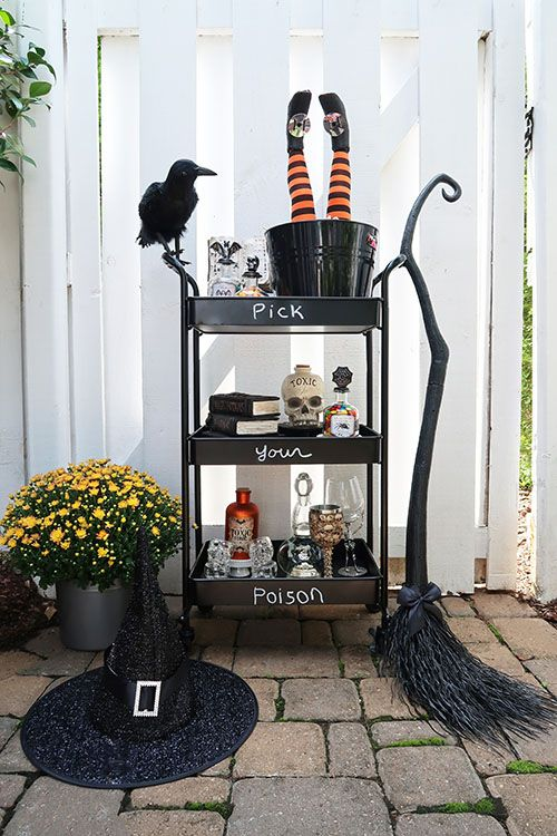 a black bar cart with witches' legs, skulls, a black bird and a broom for a bold look