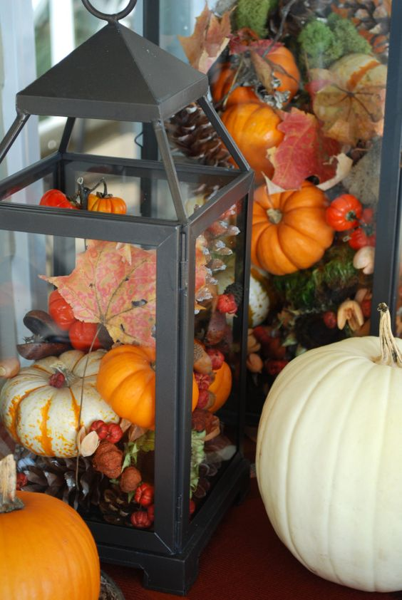 a black lantern filled with pinecones and fake pumpkins, berries and leaves for a bright fall display