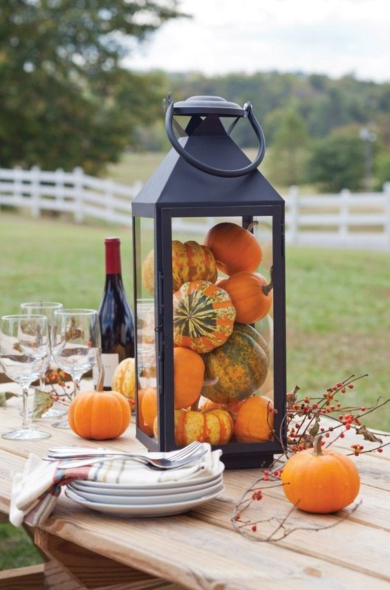 a black lantern filled with pumpkins is all you need for a cool Thanksgiving centerpiece
