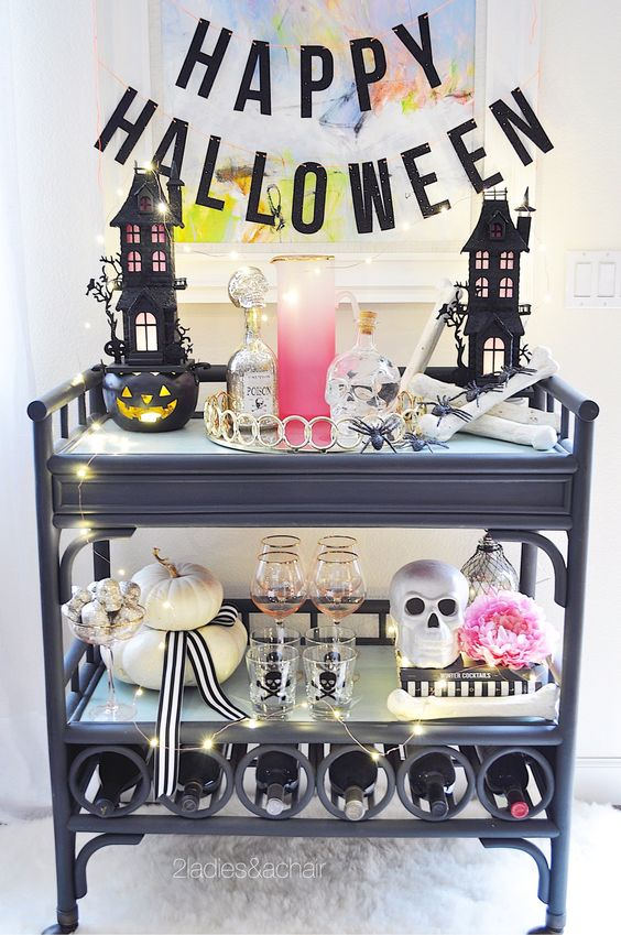 a bold Halloween bar cart with LEDs, skulls, pumpkins and black houses plus pink touches