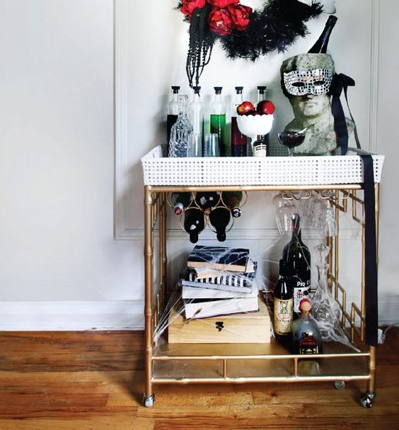 a bold bar cart with a wreath over it, poisoned apples, a bust with a bottle of wine