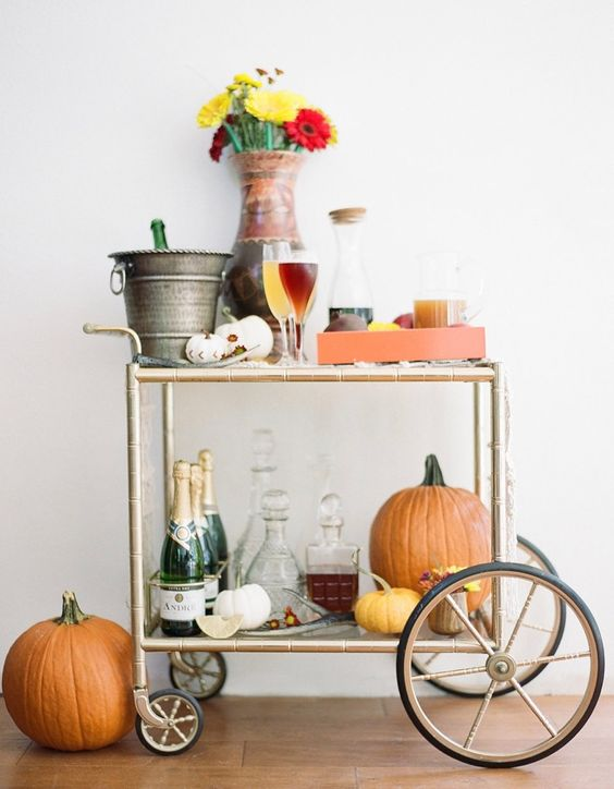 a bright Thanksgiving bar cart with pumpkins, bright flowers and colorful drinks on the cart