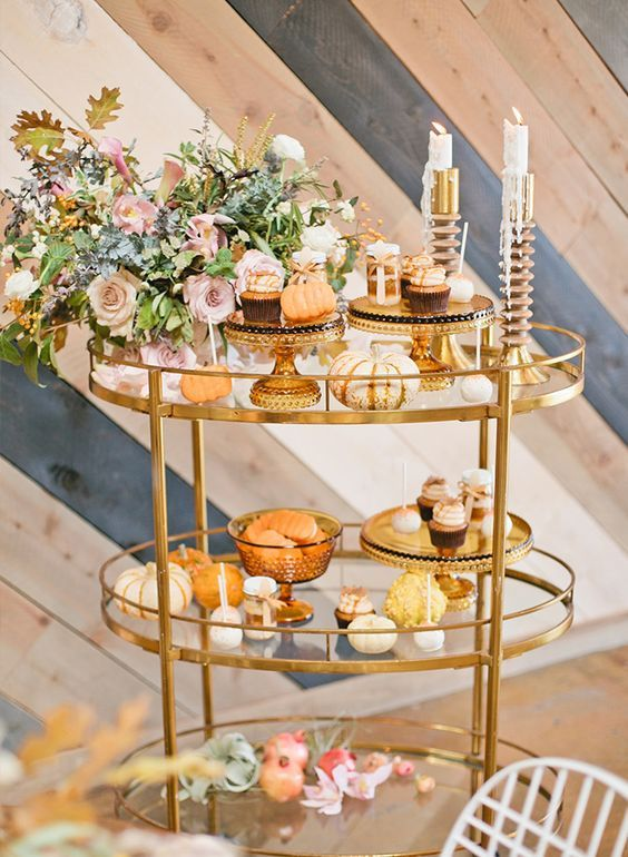 a chic Thanksgiving bar cart with a lush floral centerpiece, glass stands and bowls, candles and pumpkins