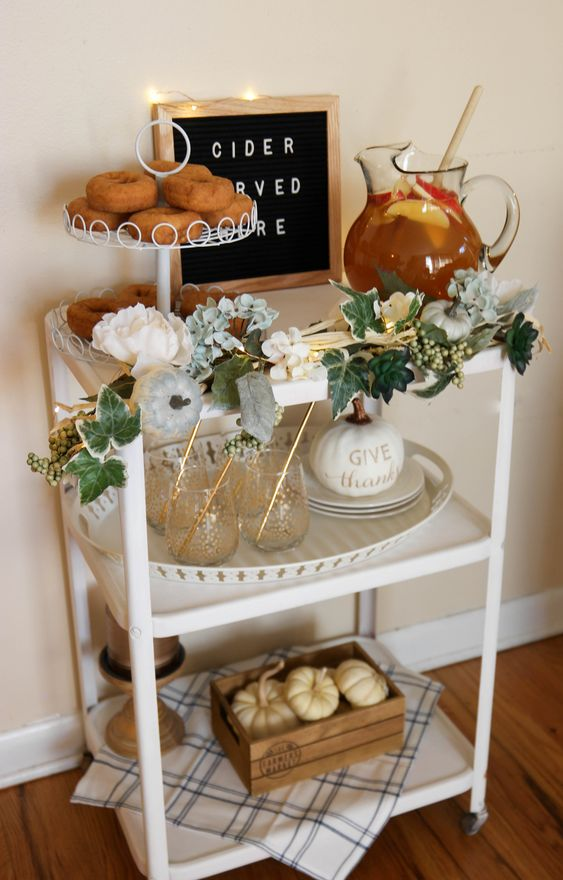 a chic bar cart with fake greenery and flower garland, faux pumpkins and a sign with lights