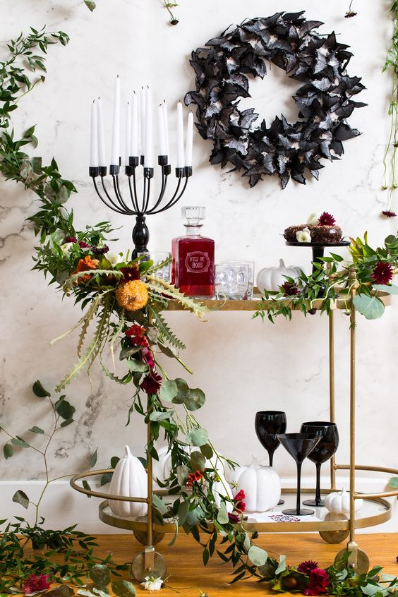 a dramatic bar cart with black glasses, a candelabra, a black butterfly wreath and a lush greenery garland