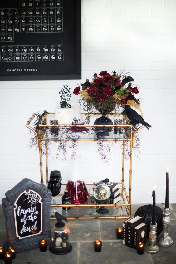 a fantastic bar cart with a black bird, a lush floral centerpiece, candles and black pumpkins