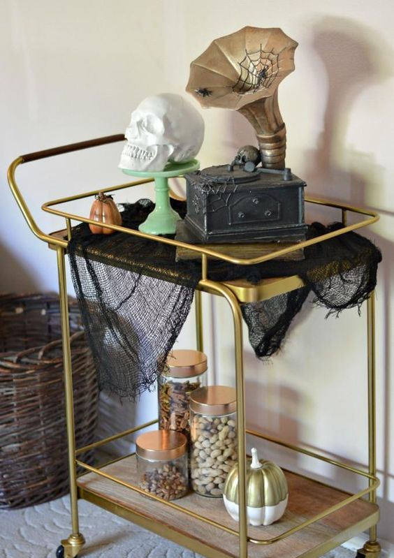 a gold bar cart with black spiderweb, a fake skull and some pumpkins