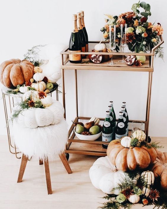 a gorgeous Thanksgiving bar cart with pears and apples, pomegranates, fall blooms and pumpkins around