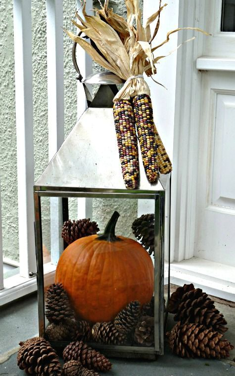 a large lantern filled with pinecones and a large orange pumpkin plus corn on top for a rustic feel