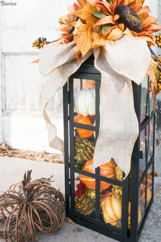 a large lantern filled with pinecones and fake veggies, with a burlap bow and fake leaves on top