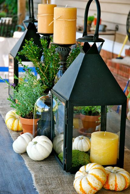 a large metal lantern with moss, a candle and fake pumpkins and pumpkins around the lantern, too
