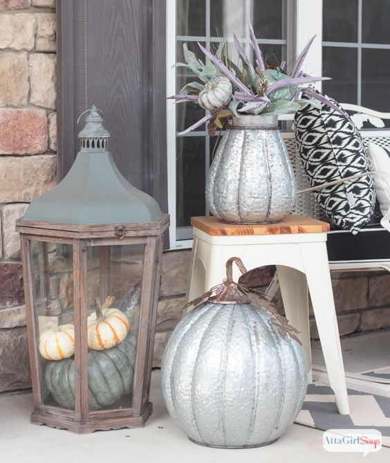 a large vintage lantern of wood with natural pumpkins inside is a gorgeous idea for a vintage or rustic porch