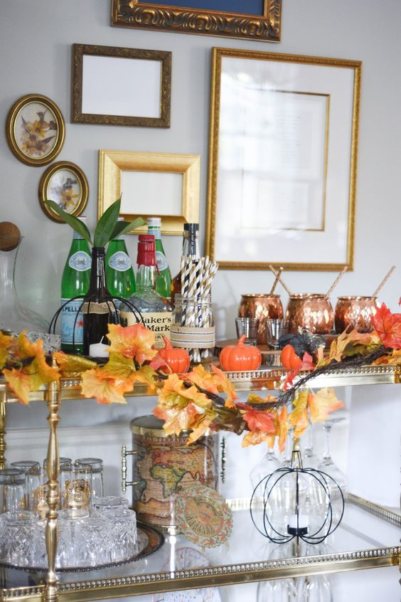 a refined bar cart with little fake pumpkins, a faux leaf garland and copper mugs