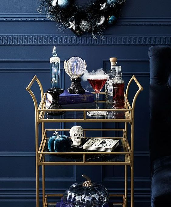 a simple yet very refined bar cart with fabric pumpkins, candles, skulls and a glass ball