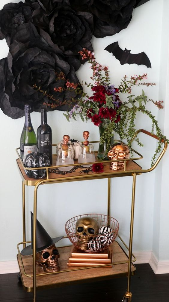 a sophisticated bar cart with metallic skulls, black and white pumpkins, a lush floral decoration and paper flowers
