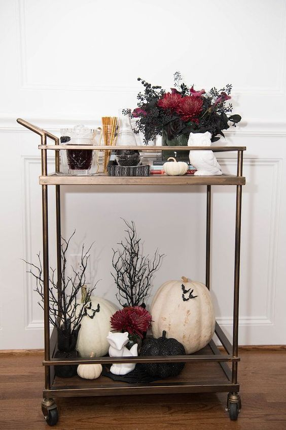 a spooky Halloween bar cart with a floral centerpiece, a pumpkin arrangement and fake trees