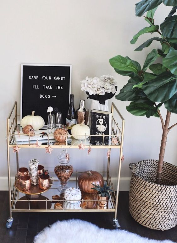 a stylish bar cart with copper touches, faux pumpkins, white blooms and a modern sign