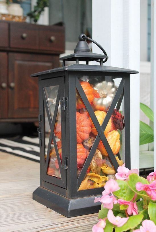 a vintage lantern filled with fake leaves and pumpkins in bold colors will last long and is easy to make