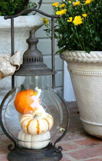 a whimsy vintage lantern with fake pumpkins is a great decoration for porches or tables