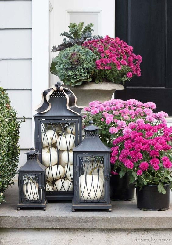 black vintage lanterns filled with white pumpkins are amazing to style your porch for fall and Thanksgiving