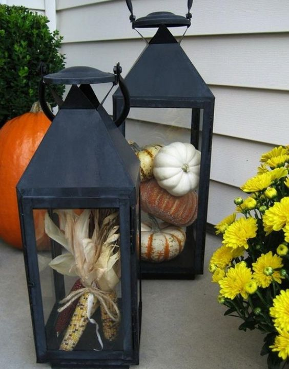 blakc metal lanterns with corn and real pumpkins are harvest-like and cool for Thanksgiving decor