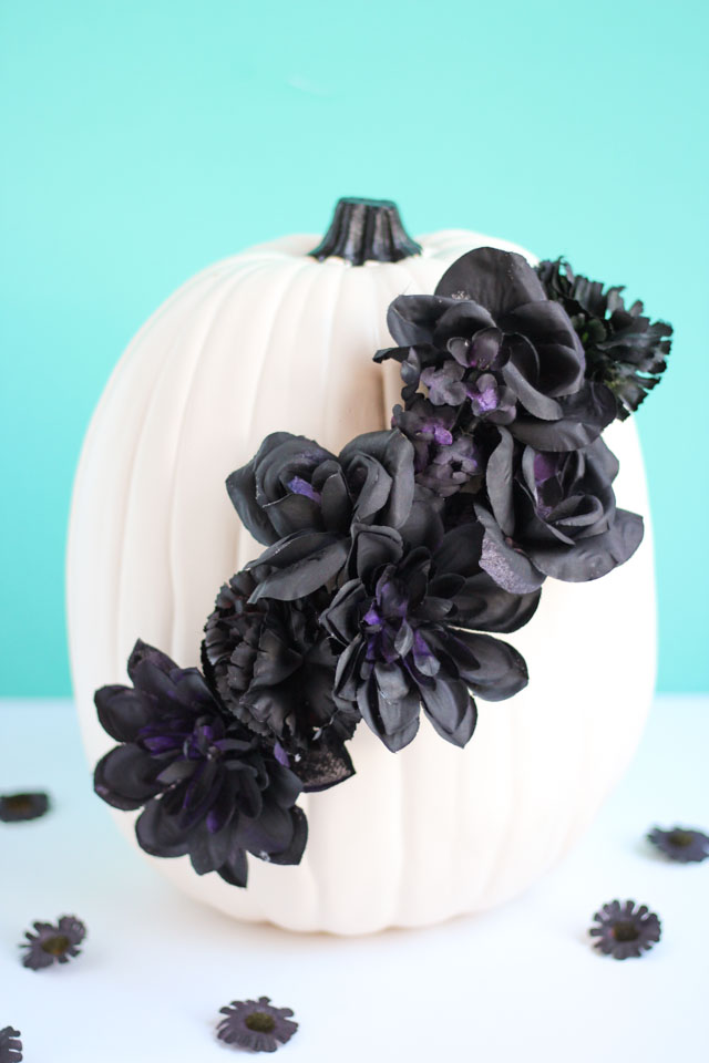 DIY white pumpkin with black fake flowers (via www.designimprovised.com)