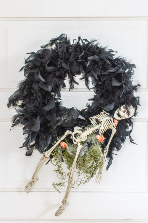 DIY creepy Halloween wreath of black feathers, a skeleton and some greenery (via diyinpdx.com)