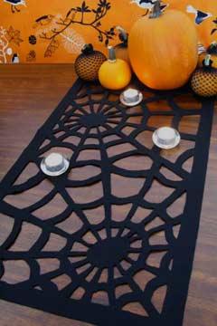 DIY cutout black spiderweb table runner of felt (via www.shelterness.com)