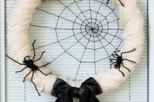 DIY spiderweb Halloween wreath with cheesecloth and wire spiders