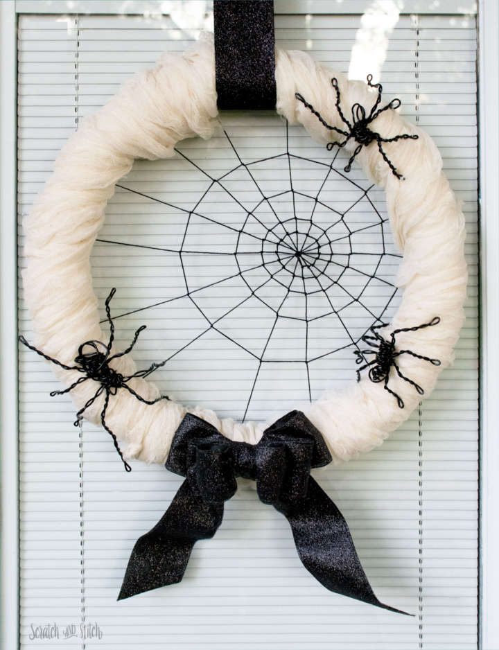 DIY spiderweb Halloween wreath with cheesecloth and wire spiders (via scratchandstitch.com)