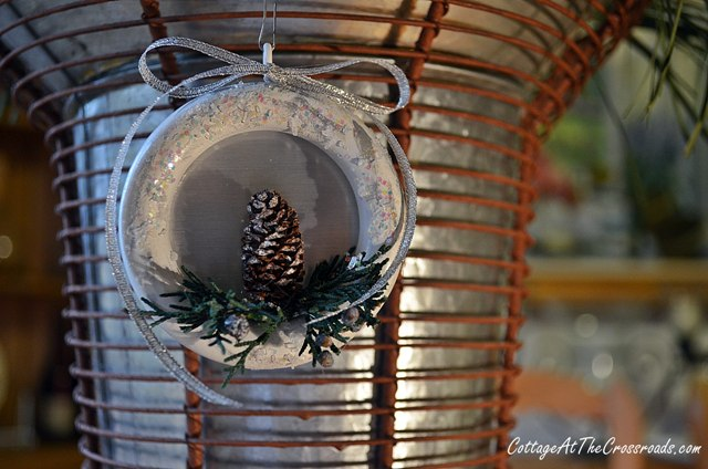 DIY Christmas ornament of a wooden ring, a pinecone and fake evergreens
